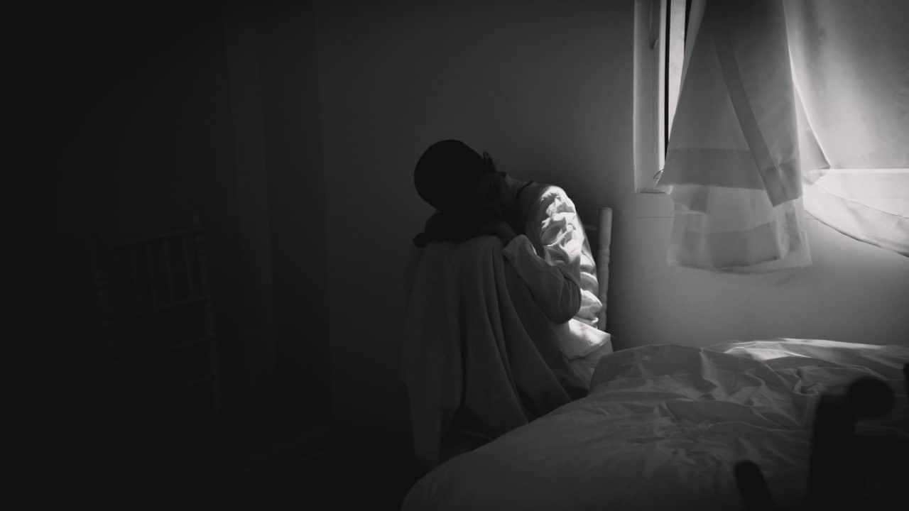 בחורה יושבת לבדה בחושך